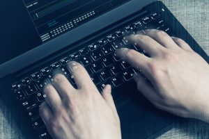 hacker's hands on laptop keyboard